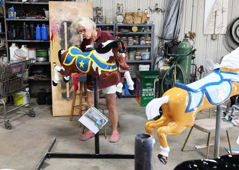 Bubbles Mensch works on one of 18 horses that will be part of the new carousel at this year's Power Show. PHOTO BY JEREMY WALTNER